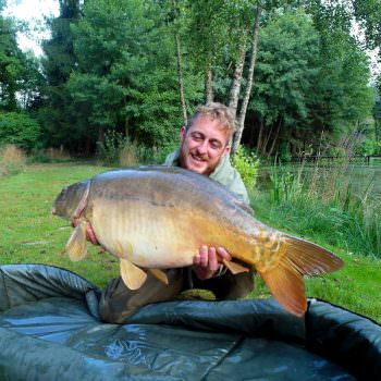 angler with 28lb mirror carp