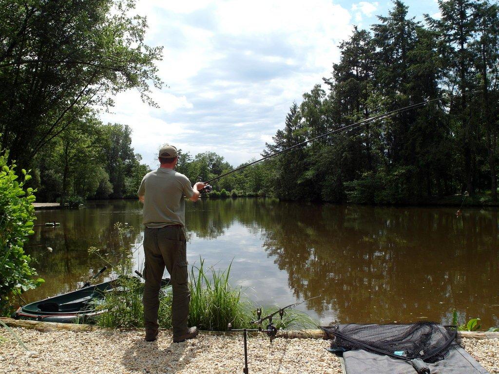 angler casting in estate lake at french carp lake