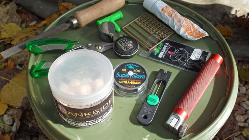 carp rig components and sharpening kit on bucket