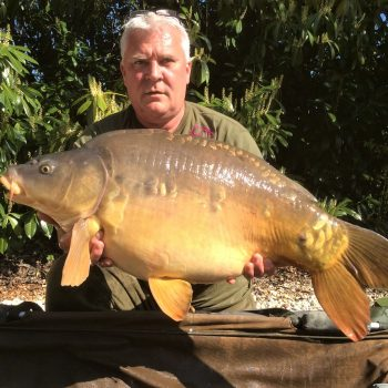 Carp angler in france nik with a mirror carp of 32 pounds