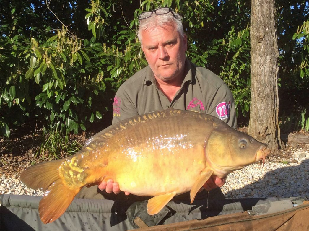 Carp angler in France Nik with a mirror carp of 30lbs