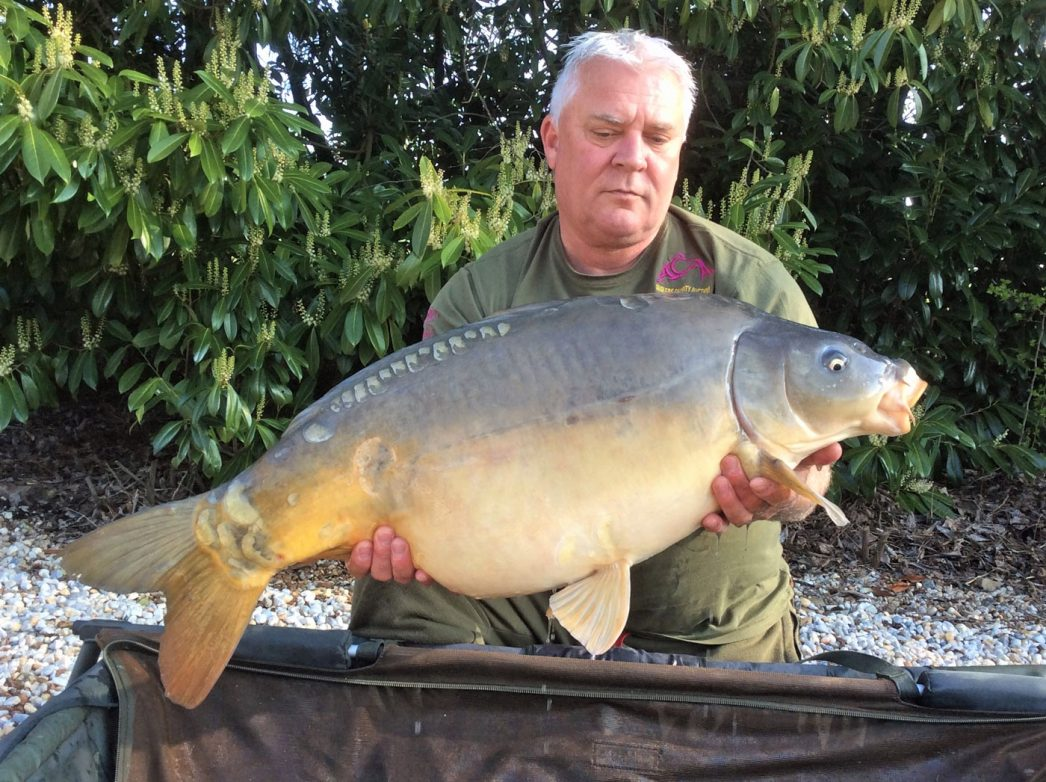 carp fishing in france angler nik with a mirror carp of 31lbs