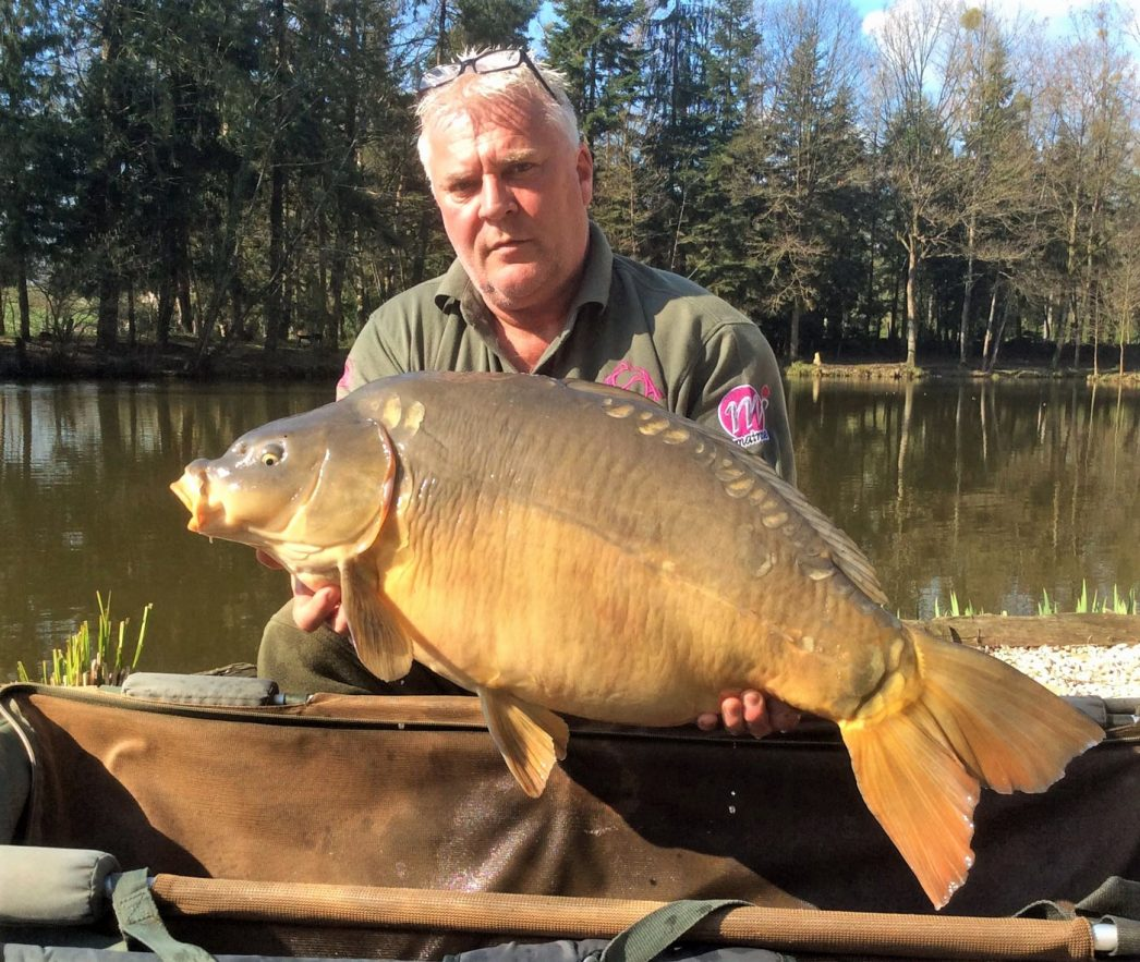 Carp angler in France Nik with a mirror carp of 36lbs