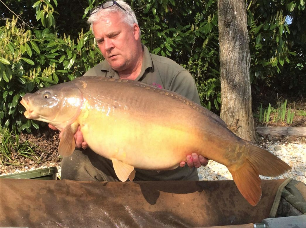 Carp angler in France Nik with a mirror carp of 37lbs
