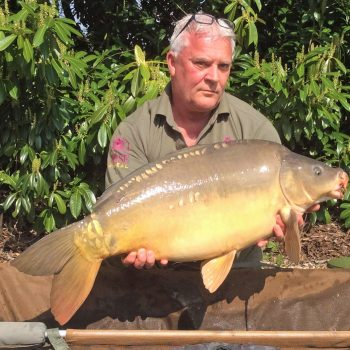 Carp angler in France Nik with a mirror carp of 28lbs 8oz