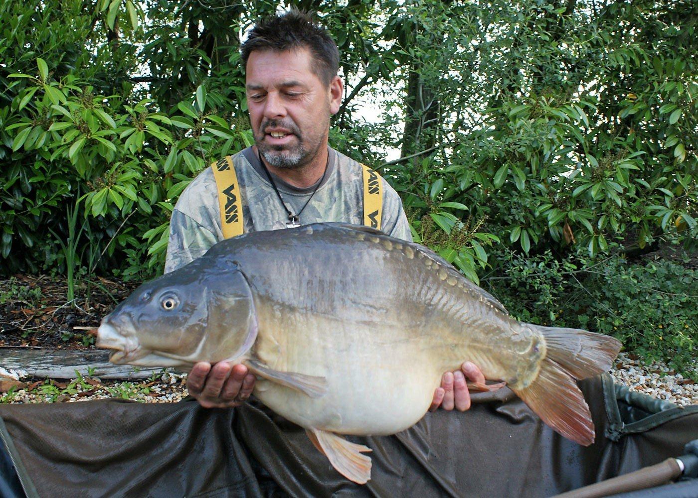 carp fishing france angler with a mirror carp of 34lbs