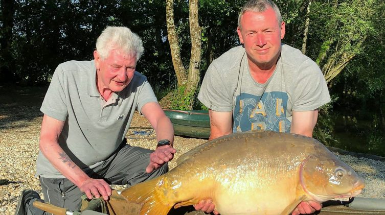 carp angler in france fishing on holiday with his father and a 39lb mirror carp