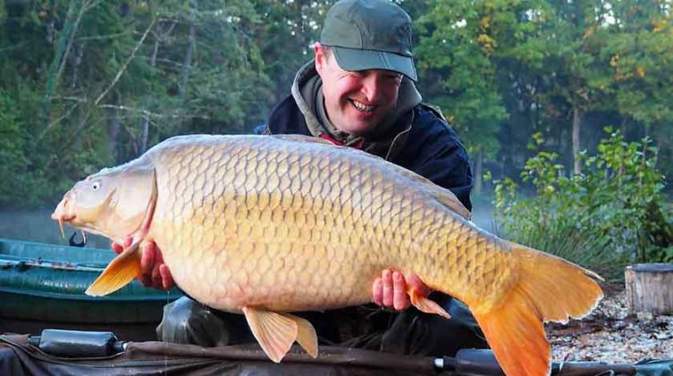 angler with common carp on fishing holiday