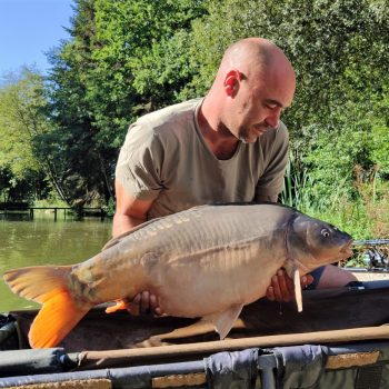angler with 31lb mirror carp in france