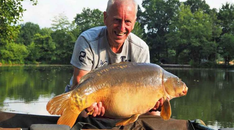 angler with mirror carp in france at beausoleil