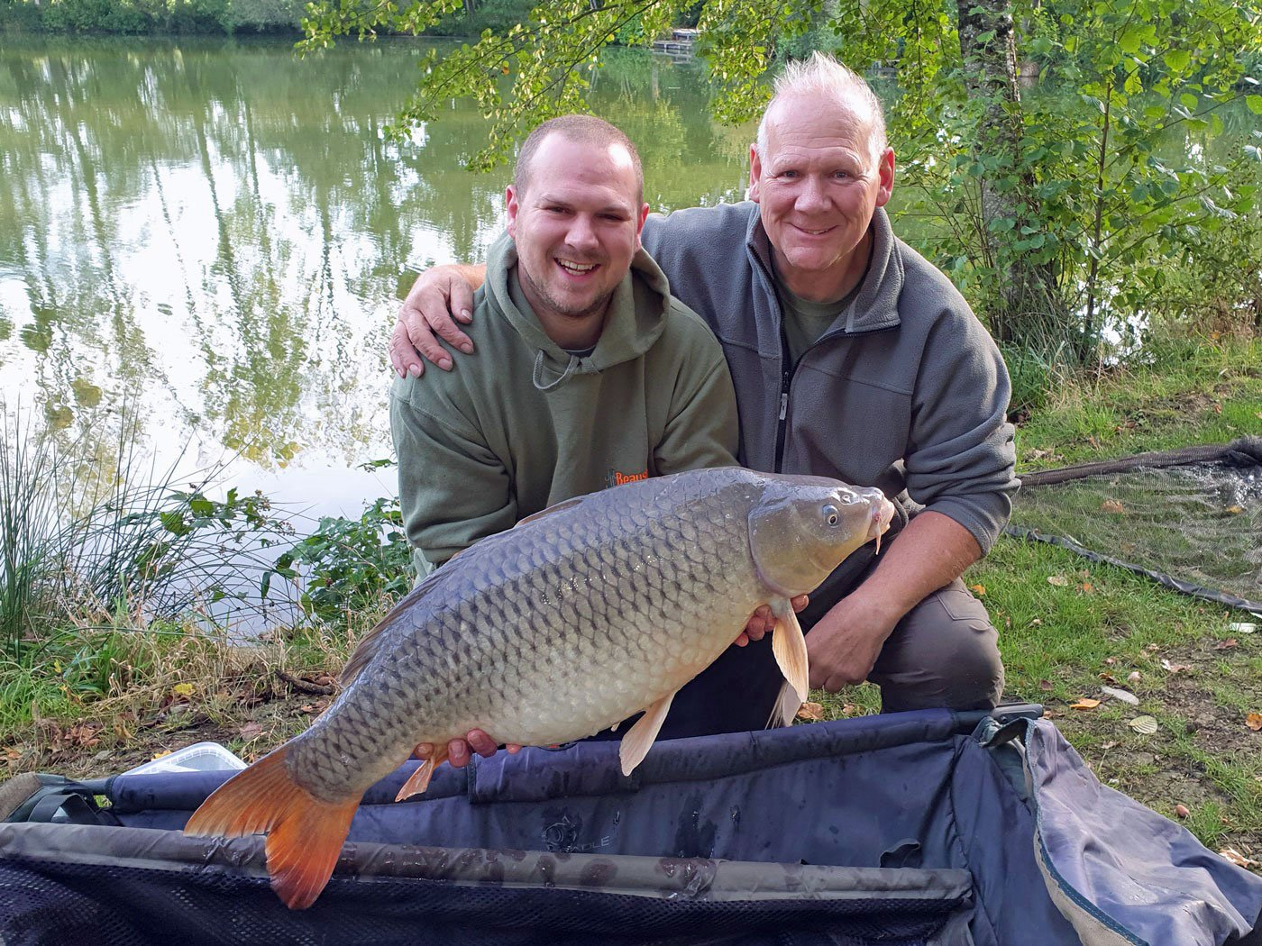 father and son carp fishing in france with a 29 pound common carp